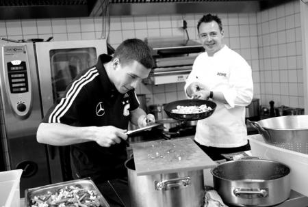Spielerwechsel an den Herd – Lukas Podolski macht den Küchenassistenten für Holger Stromberg. Foto © Michael Agel