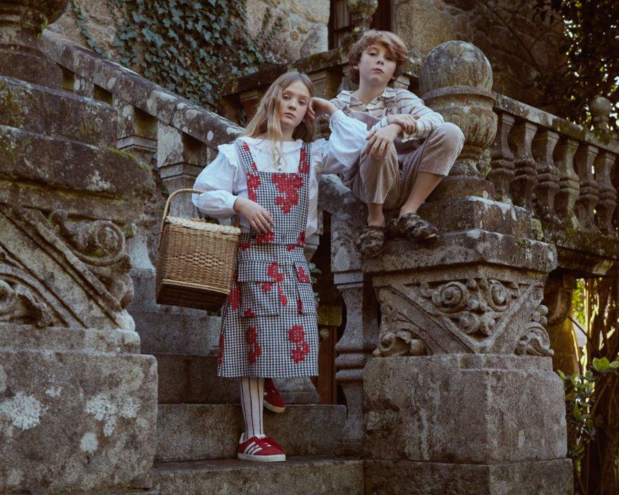 Gretel trägt im Herbst 2018 ein geblümtes Schürzenkleid, Hänsel eine Cord-Dungaree und Fellpantoffeln für die Straße!