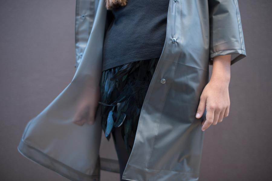 Spannender Materialmix – ein Minirock aus Federn schimmert unter dem transparenten Regenmantel