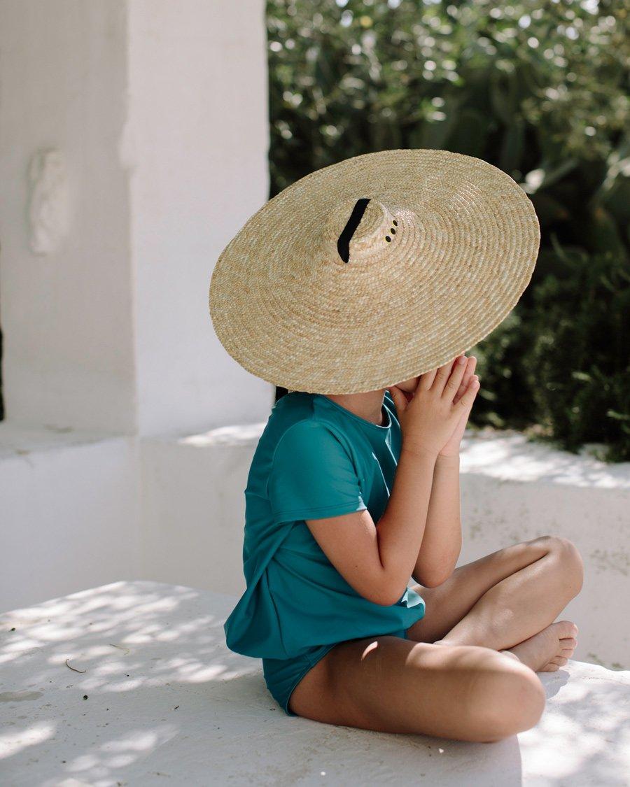 So elegant kann Sonnenschutz aussehen! Den neuen CANOPEA-Einteiler krönt ein handgefertigter Strohhut von GOODBYE LORETTE
