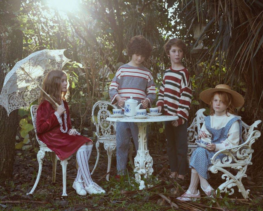 Eine entzückende Teegesellschaft: Unter dem Baum sitzt Alice in einem beerenroten Samtkleid von FISH & KIDS