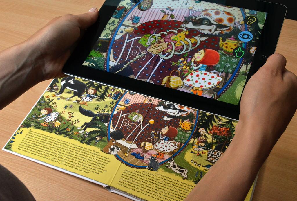 """Die Tablet-Kamera erkennt den Hotspot auf der Buchseite und ruft ein neues Bild auf das Display (Aus dem Bilderbuch """"Mein großer Märchenschatz"""", LeYo!-Reihe, Carlsen)"""